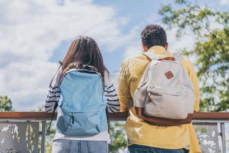 Photo pour Vue arrière des voyageurs multiculturels restant avec des sacs à dos - image libre de droit