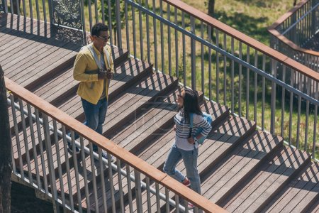 Photo for Happy multicultural friends walking with backpacks on stairs - Royalty Free Image