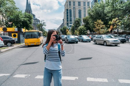 Photo for Young woman taking photo while standing on street with cars - Royalty Free Image
