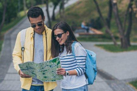 glücklicher Mischlingsmann mit Sonnenbrille und fröhliches Mädchen, das auf die Karte schaut