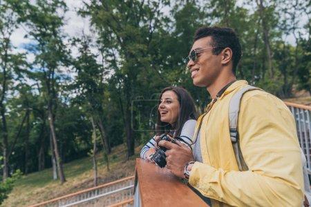 happy mixed race man holding digital camera near cheerful girl in park