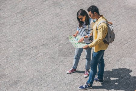 overhead view of mixed race man and attractive woman holding map