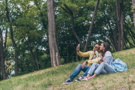 happy mixed race man taking selfie with cheerful girl while sitting on grass