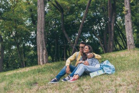 Photo pour Homme heureux mélangé de course étreignant la fille gaie tout en s'asseyant sur l'herbe - image libre de droit