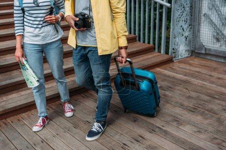 Photo pour Vue recadrée d'une femme et d'un homme multiculturels marchant avec des bagages bleus - image libre de droit