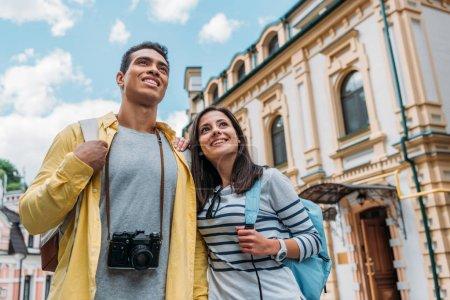 Photo pour Vue à angle bas de heureux mixte homme et gaie fille souriant contre le ciel bleu avec des nuages - image libre de droit