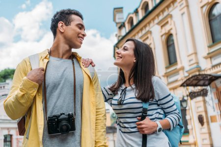 low angle view of happy mixed race man looking at cheerful girl against blue sky with clouds