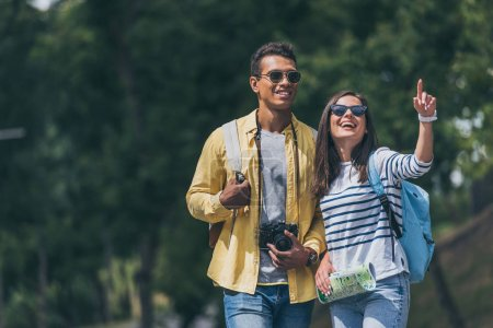 Photo pour Heureux fille dans lunettes de soleil pointant avec doigt près mixte race homme avec appareil photo numérique - image libre de droit