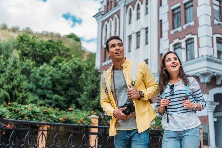 Foto de Chica feliz tocando la mochila mientras está de pie con el hombre de la raza mixta cerca de la construcción - Imagen libre de derechos