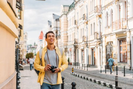 Photo for Happy mixed race man smiling while holding digital camera near buildings - Royalty Free Image