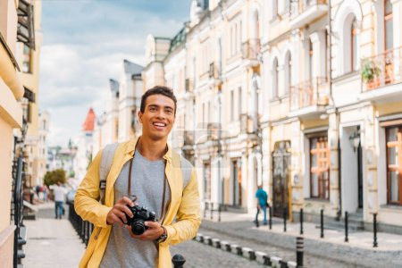 Photo for Cheerful mixed race man smiling while holding digital camera near buildings - Royalty Free Image