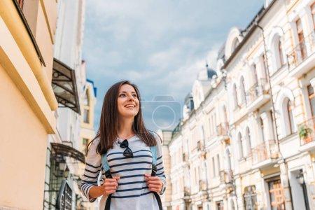 Photo pour Vue bas d'angle de fille heureuse avec le sac à dos près des bâtiments - image libre de droit