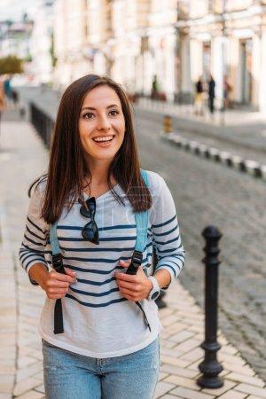 Photo pour Heureuse fille touchant sac à dos et souriant près du bâtiment - image libre de droit
