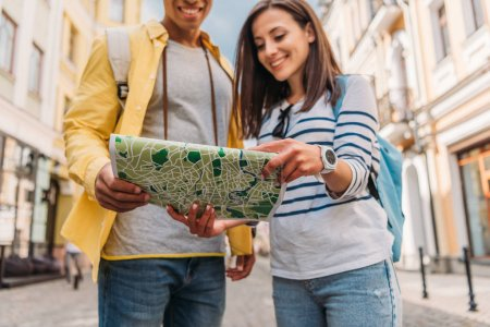 cropped view of cheerful mixed race man holding map near happy girl