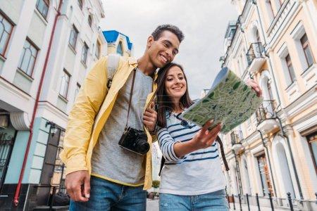 Niedrigwinkel-Ansicht des glücklichen Mischlingshundes, der auf die Karte in der Nähe des glücklichen Mädchens schaut