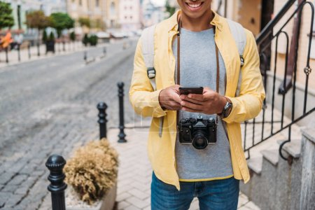 Photo for Cropped view of happy mixed race man using smartphone outside - Royalty Free Image