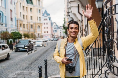 Photo for Happy mixed race man holding smartphone while waving hand - Royalty Free Image