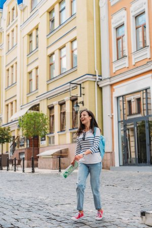 Photo for Happy young woman walking on street and holding map - Royalty Free Image