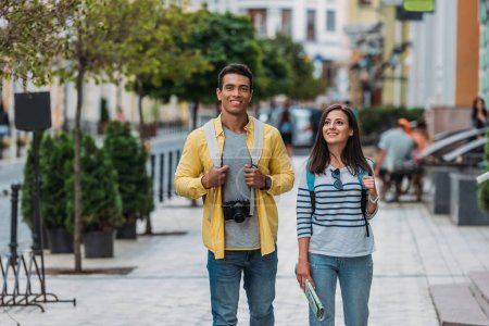 Photo for Happy woman walking with handsome bi-racial man on street near buildings - Royalty Free Image