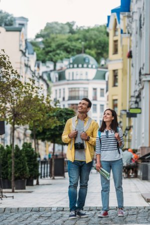 happy woman standing with cheerful bi-racial man on street near buildings