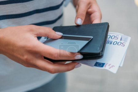 cropped view of woman holding euro banknotes and credit card with wallet