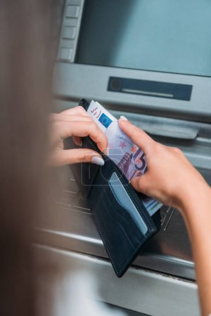 selective focus of woman putting money in wallet near atm machine