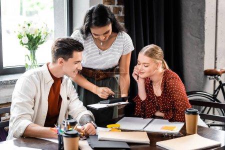 Photo pour Trois amis multiethniques assis à table et regardant la calculatrice dans l'appartement - image libre de droit