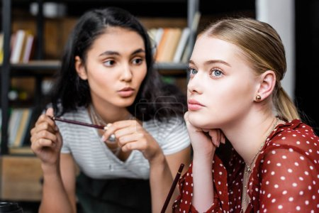 Photo for Attractive multiethnic students talking and looking away in apartment - Royalty Free Image