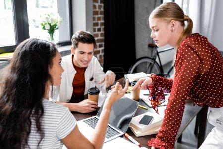 Photo pour Étudiants multiethniques souriant et regardant l'ordinateur portatif dans l'appartement - image libre de droit