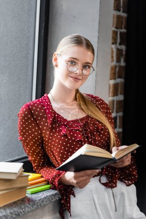 attractive and smiling student in glasses holding book in apartment