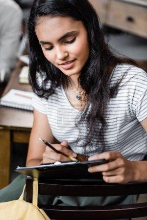 atractivo y bi-racial estudiante sosteniendo portapapeles y lápiz en el apartamento