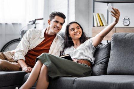 Photo pour Étudiants multiculturels heureux souriant et prenant le selfie dans l'appartement - image libre de droit