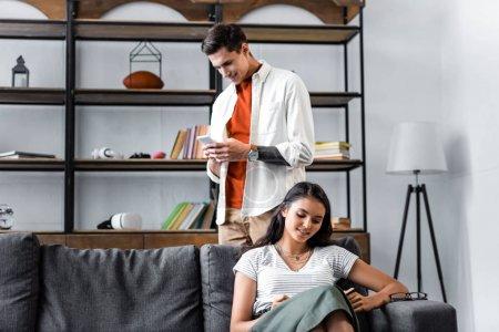 Foto de Estudiantes multiculturales sentados en el sofá y usando el teléfono inteligente en el apartamento - Imagen libre de derechos