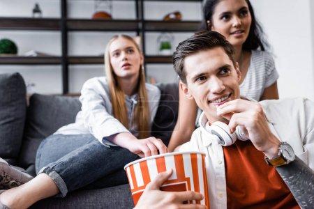 Photo pour Foyer sélectif d'amis multiculturels souriant et mangeant du pop-corn dans l'appartement - image libre de droit