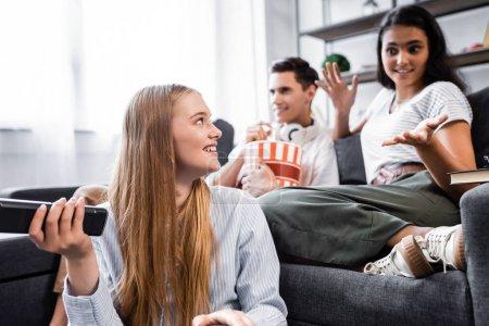 Photo pour Foyer sélectif des amis multiculturels souriant et mangeant le maïs soufflé dans l'appartement - image libre de droit
