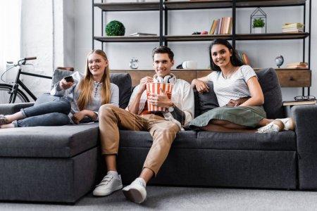 Foto de Amigos multiculturales sentados en el sofá y comiendo palomitas de maíz en el apartamento - Imagen libre de derechos