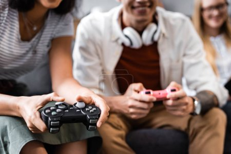 Photo for KYIV, UKRAINE - JULY 10, 2019: cropped view of multicultural friends playing video game in apartment - Royalty Free Image