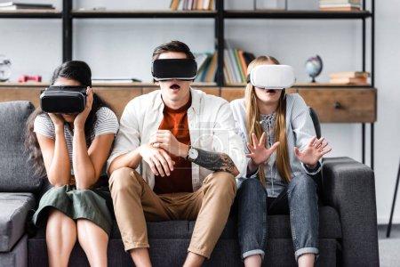 Photo pour Amis multiculturels choqués avec des casques de réalité virtuelle assis sur le canapé - image libre de droit