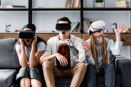amigos multiculturales con auriculares de realidad virtual sentados en el sofá