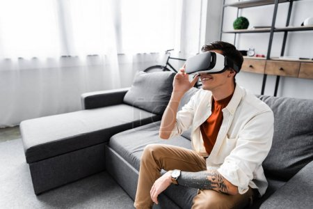 Photo for Emotional man in shirt with virtual reality headset in apartment - Royalty Free Image