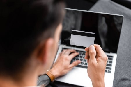 selective focus of man holding credit card and using laptop in apartment
