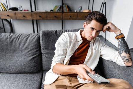 Photo pour Bel homme dans la chemise s'asseyant sur le sofa et retenant le contrôleur à distance dans l'appartement - image libre de droit