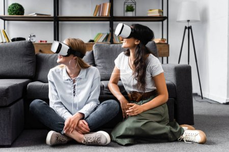 Photo pour Amis multiculturels avec des casques de réalité virtuelle assis sur le sol dans l'appartement - image libre de droit
