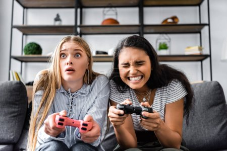 Photo for KYIV, UKRAINE - JULY 10, 2019: multicultural friends sitting on sofa and playing video game in apartment - Royalty Free Image