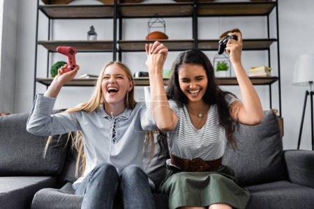 Photo pour KYIV, UKRAINE - 10 JUILLET 2019 : amis multiculturels assis sur le canapé et jouant au jeu vidéo en appartement - image libre de droit