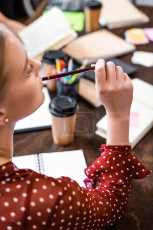 selective focus of student in blouse holding pencil in apartment