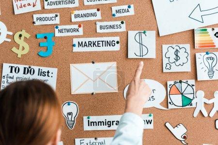 Photo pour Vue recadrée de femme d'affaires pointant avec le doigt aux notes collantes sur le panneau d'affichage - image libre de droit