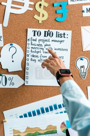 Photo for Cropped view of businesswoman pointing with finger at to do list on notice board - Royalty Free Image