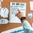 cropped view of businesswoman pointing with finger at to do list on notice board