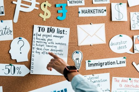 Photo for Cropped view of businesswoman pointing with finger at to do list near lettering on notice board - Royalty Free Image